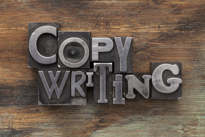 copywriting - text in vintage letterpress metal type blocks on a grunge painted wood